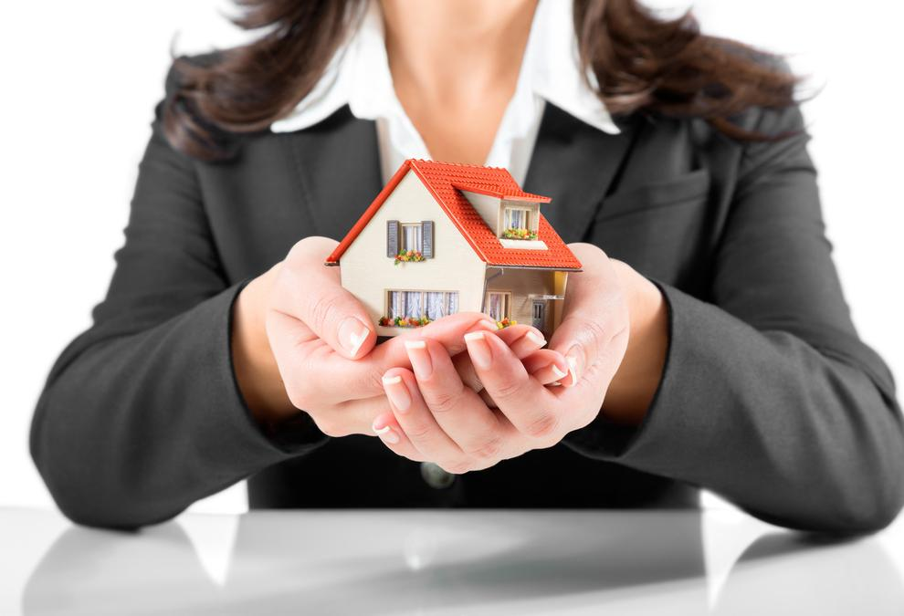 insurance and protection concept - realtor woman gives a house